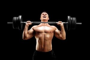 guapo deportista levantando un peso pesado foto