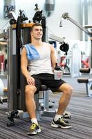 Hombre sonriente haciendo ejercicio en la máquina de gimnasio