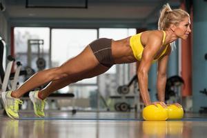 Mujer haciendo ejercicio flexiones en bolas amarillas foto