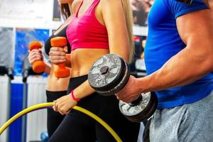 Group of people  working with dumbbells and hoop  at gym photo