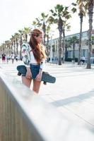 Stylish woman skateboarder standing with her penny board outdoors