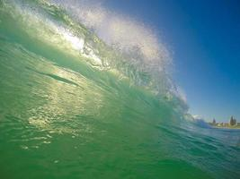 Green wave breaking on the beach against a blue sky