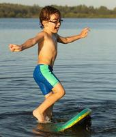 Little boy at river trying to stand on body board