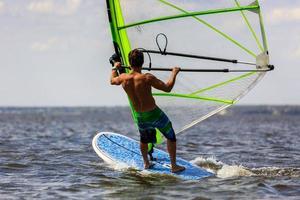vista trasera del joven windsurfista foto