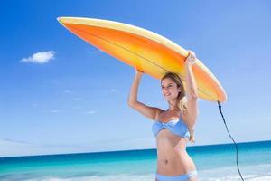 jolie blonde femme tenant une planche de surf