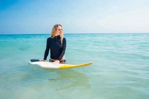 mulher com uma prancha de surf no oceano
