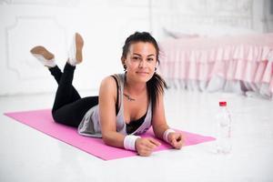 Mujer joven relajante después de hacer ejercicio en casa acostado en yoga foto