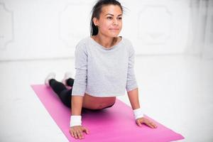 Girl doing warming up exercise for spine, backbend, arching stretching photo