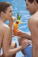 pareja compartiendo una bebida tropical junto a la piscina foto