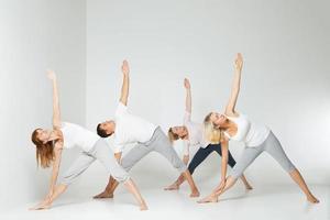 Grupo de personas relajantes y haciendo yoga en blanco