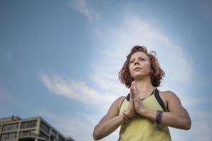 jovem de cabelos vermelha fazendo yoga (mãos de oração) (pose de árvore)
