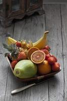 Fruit bowl with fruits, knife on wood