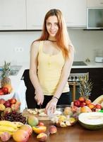 mujer cortando banana para ensalada de frutas foto