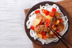 pork in sweet and sour sauce with noodles top view photo
