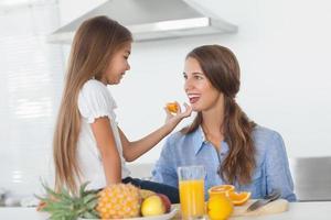 menina dando um segmento laranja para sua mãe
