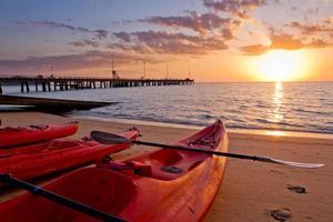 tres kayaks rojos en la playa al amanecer foto