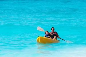 Father and son on a kayak in tropical ocean