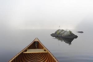 canoa de cedro y rocas en un brumoso lago ontario