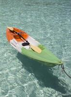 Colorful plastic canoe on water sandy beach.