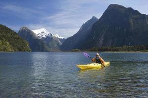 hombre en kayak en el lago de montaña