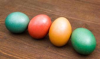 Oblique row of colorful eggs on wood