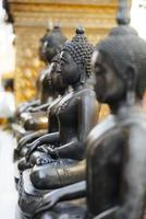 linha de estátuas budistas de metal escuro
