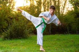 Niño en kimono blanco durante el entrenamiento de ejercicios de karate en verano