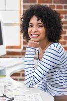 sonriente mujer editor de fotos usando la computadora en la oficina