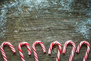 bastones de nieve y dulces sobre fondo de madera foto