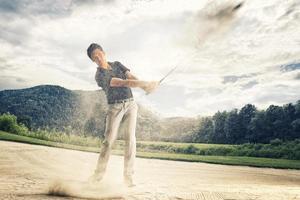 Golfista en la trampa de arena. foto