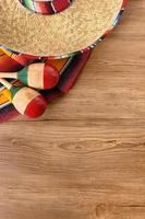 Mexican sombrero and blanket on pine wood floor photo