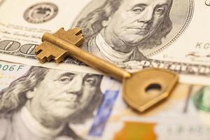gold key on hundred dollar bills photo