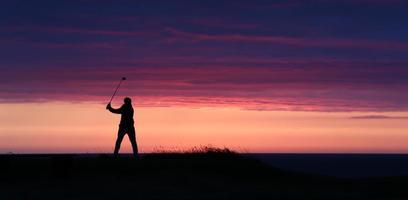 El último viaje del día del golfista al atardecer. foto