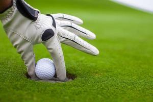 La mano del hombre poniendo la pelota de golf en el hoyo en campo verde foto
