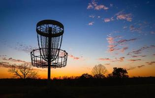 Silhouette of disc golf basket against sunset photo