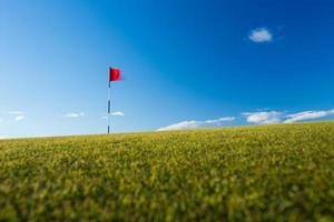 Red golf flag on a green