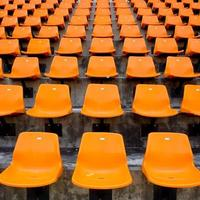Orange empty stadium seats in arena photo