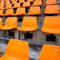 Orange empty stadium seats in arena