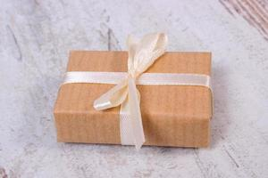 Wrapped gift for Christmas on old wooden background photo