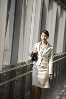 Young business woman walking along inside station photo