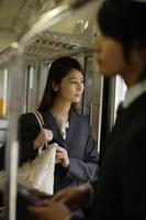 Business woman looking at outer scenery from inside of train