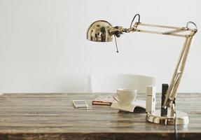 Work desk, lamp,chrome, mobile phone coffee and notepad photo