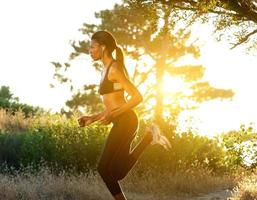 Fit young woman running outdoors photo