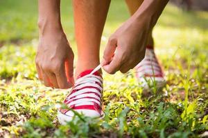 Mujer atando sus zapatos antes de correr en el parque