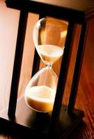 Wooden hourglass with running sand photo