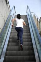 mujer corriendo en las escaleras mecánicas foto