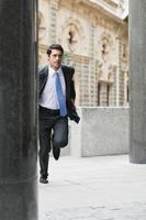 Businessman running on city street photo