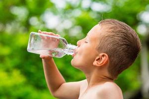 Niño bebiendo agua limpia del grifo de una botella de plástico transparente