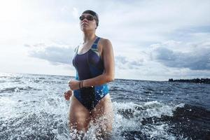 Young woman athlete running out of water photo