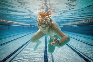 Boy swimming under water photo